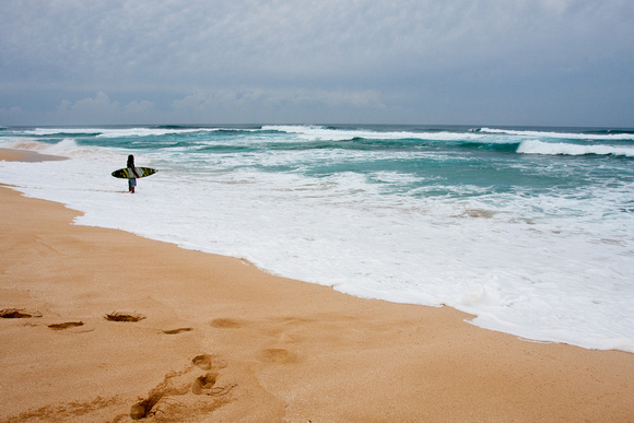 Surfer contemplating his entry into the North Shore waters, Oahu